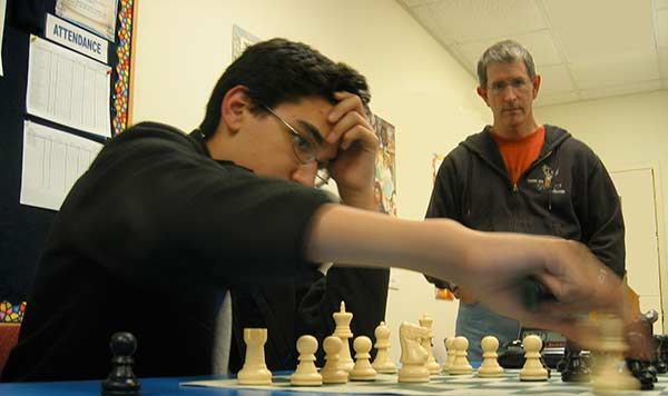 This a photograph of David Marsh (R) watching Alborz Bejnood (L) play chess.