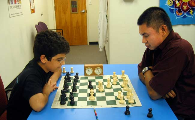 This a photograph of Keith Eatherly (R) playing chess with Aram Bejnood (L).